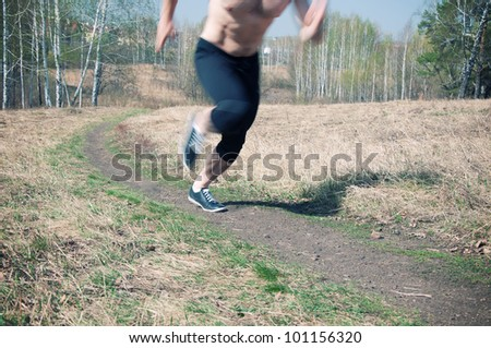 Low section of man in sportswear jogging on gravel path on a sunny day, blurred motion - stock photo