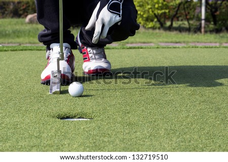 Low section of man's feet with golf club and ball