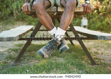 Low section of man sitting on picnic table - stock photo