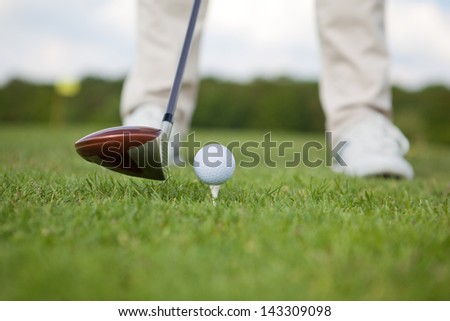 Low section of man with golf club and ball on course - stock photo