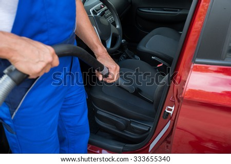 Low section of mature worker vacuuming car with vacuum cleaner - stock photo
