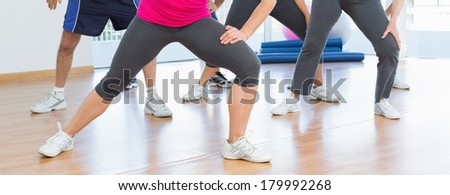 Low section of people doing power fitness exercise at yoga class in fitness studio - stock photo