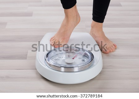 Low Section Of Person Standing On Weighing Scale - stock photo