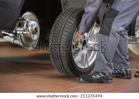 Low section of repairman fixing car's tire in repair shop - stock photo