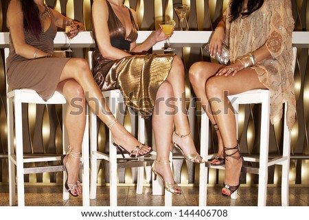 Low section of three stylishly dressed women sitting legs crossed at the bar - stock photo