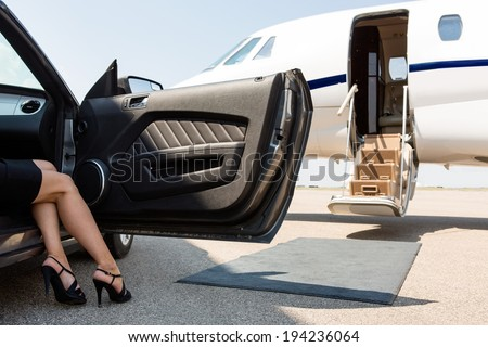 Low section of wealthy woman stepping out of car parked in front of private plane - stock photo