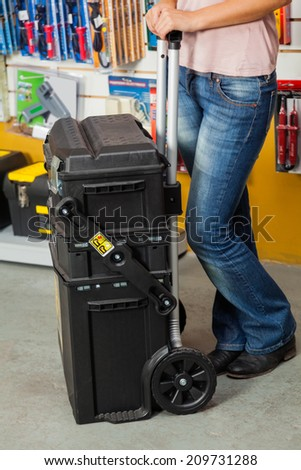 Low section of woman holding tool case in hardware store