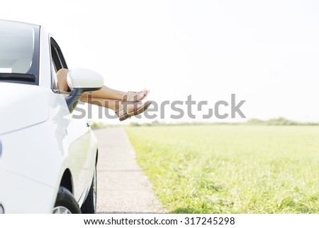 Low section of woman relaxing in car on country road - stock photo