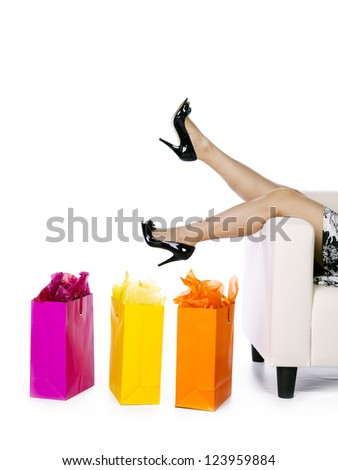 Low section of woman relaxing on couch after long day shopping - stock photo