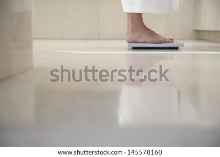 Low section of woman standing on weighing scale in bathroom - stock photo