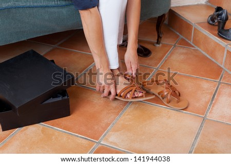 Low section of woman trying new sandals in store - stock photo