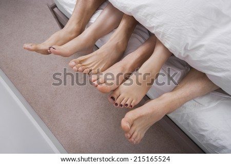 Low section of woman with two men in bed - stock photo