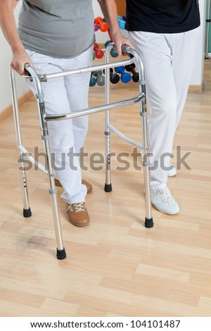 Low section of woman with walker and trainer on wooden floor