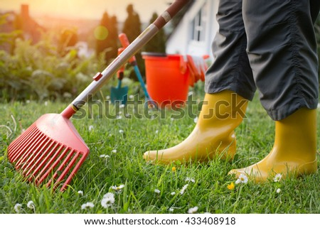 Low section of woman with yellow gumboots working in backyard with plastic rake. Gardening equipment in background
