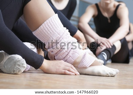 Low section of women relaxing in ballet rehearsal room - stock photo