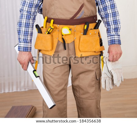 Low section of young male carpenter with spirit level and gloves at home - stock photo