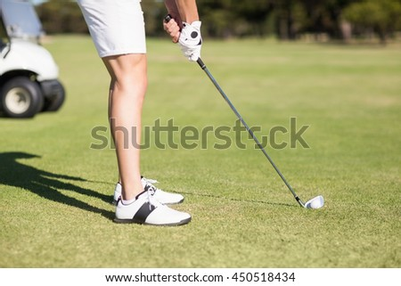 Low section of young man playing golf while standing on field - stock photo
