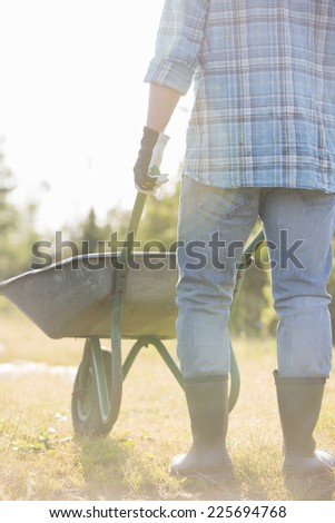 Low section rear view of man pushing wheelbarrow at garden - stock photo