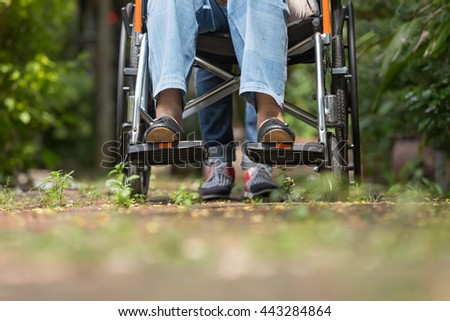 Low section shot of elderly woman in wheelchair walking with car - stock photo