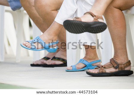 Low section view of senior people sitting together in a row - stock photo