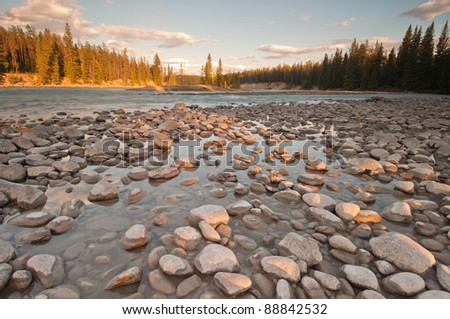 Low shot of pebbles and stones along a river with golden sunset. - stock photo