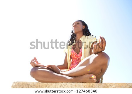 Low side view of a healthy and attractive african american woman in a yoga position meditating against a bright blue sky on a sunny day. - stock photo