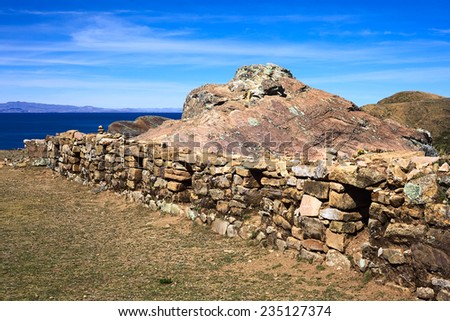 Low stone wall with openings beside the Rock of the Puma, the sacred rock formation of the Tiwanaku and Inca cultures on the Isla del Sol (Island of the Sun) in Lake Titicaca, Bolivia