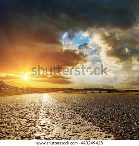 low sunset in dramatic sky over asphalt road - stock photo