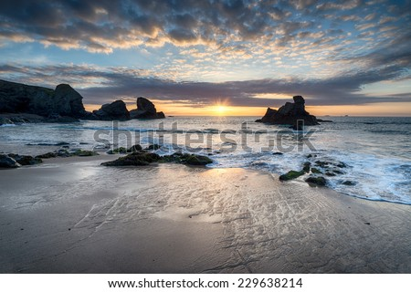 Low tide and sunset at Porthcothan Beach on the north coast of Cornwall - stock photo