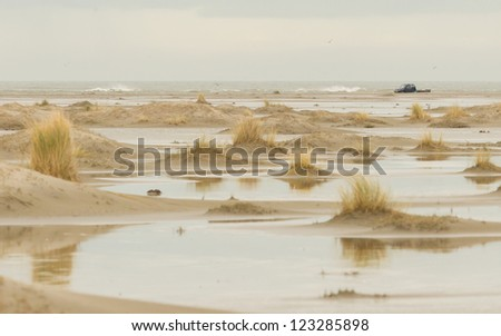 Low tide at the dunes of Ameland, dark sky, Holland - stock photo
