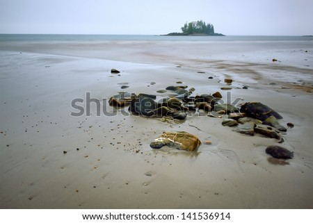 Low tide on a New England Beach with piled up rocks during a storm - stock photo