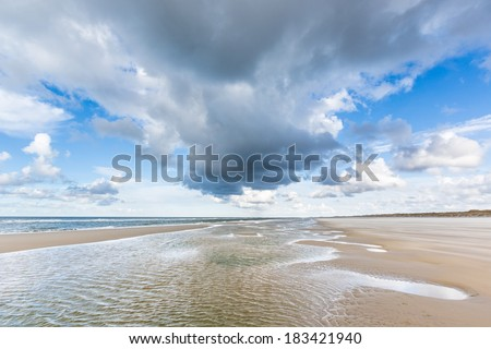 Low tide on an empty beach under a blue sky with clouds - stock photo