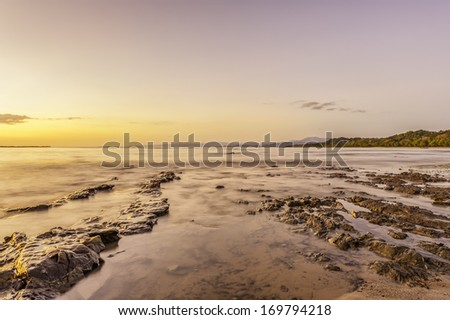 Low tide on the Pacific Coast of Costa Rica at sunset. - stock photo