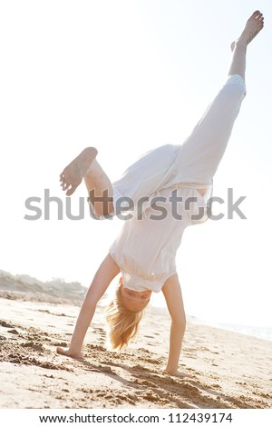 Low view of a young girl doing cartwheels on a golden sand beach with the sun rays filtering through her body during sunset. - stock photo