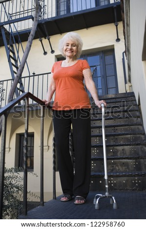 Low  view of an elderly woman with cane standing outside house - stock photo