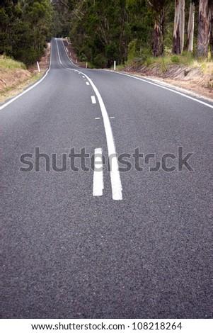 Low view of asphalt road in rural Australia - stock photo