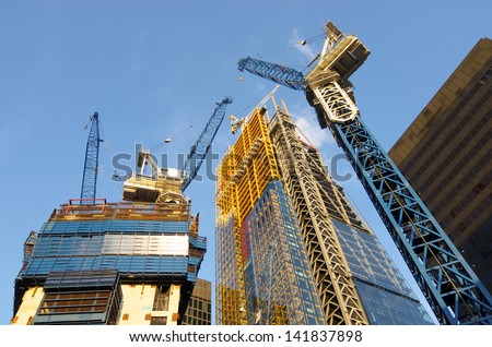 low view of the cranes to build new skyscrapers in the City of London - stock photo