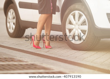 Low view of woman's legs near her white car. Lady posing for photographer for fashionable mazagine. She demonstrating slim and slender legs on high heels. Toned image. - stock photo
