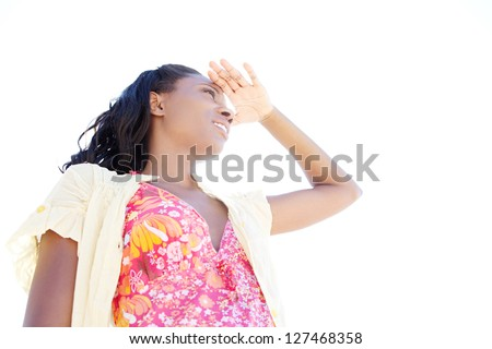 Low view portrait of an attractive black woman on holiday shading her eyes with her hand against a clean sky. - stock photo