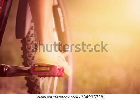 Low viewing angle of woman leg on mountain bike pedal - stock photo