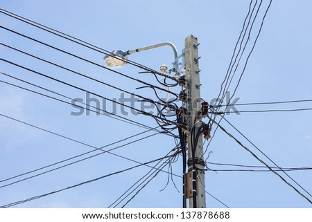low voltage electricity post and cable in sunny day - stock photo