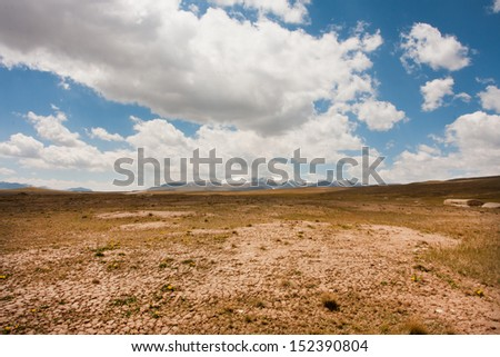 Low white clouds floating over dry land of the mountain plateau in Central Asia - stock photo
