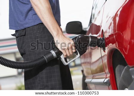 Lower body of a man refueling a car