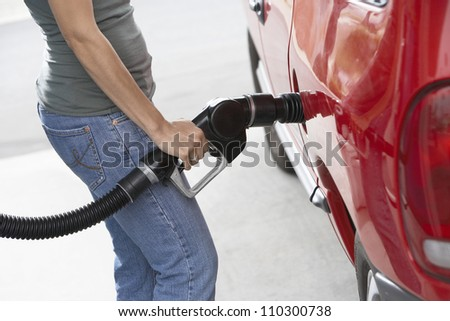 Lower body of a woman refueling her car - stock photo