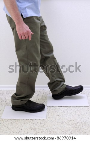 Lower body of relaxed man walking over two light gray empty paper boards. - stock photo