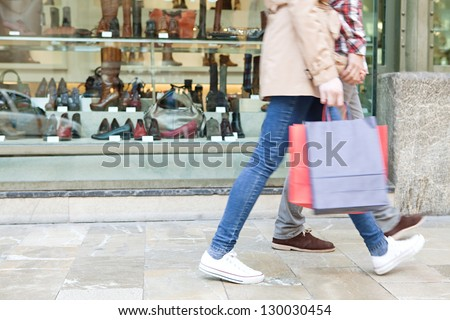 Lower body section of a young tourist couple walking by store windows and holding paper shopping bags in a destination city. - stock photo