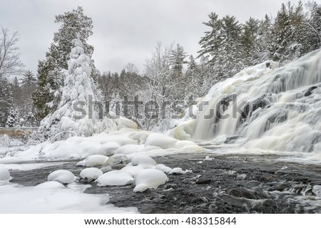 Lower Bond Falls. A beautiful waterfall flowing over the icy rocks and snow covered spruce trees.