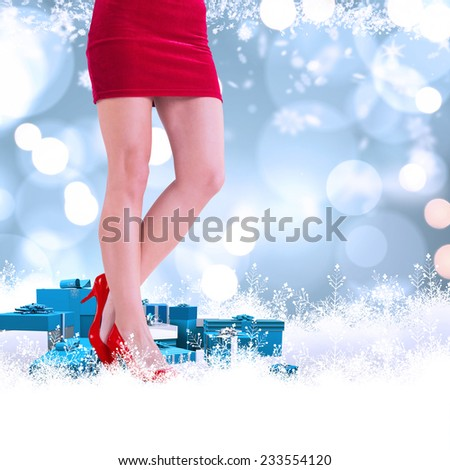 Lower half of girl in red skirt and heels against white glowing dots on blue - stock photo
