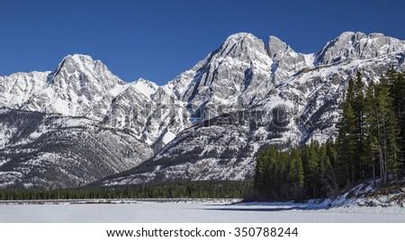 Lower Kananaskis Lake, Frozen at base of mountains - stock photo