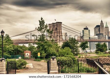 Lower Manhattan skyline and Brooklyn Bridge over Hudson, New York. - stock photo